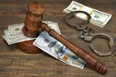 Dollar-Bargeld, Handschellen und Richterhammer auf hölzerner Tabelle Stockbild