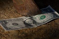 A dollar being cut with an axe Stock Photos