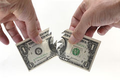 US One Dollar bill being torn in half by hands, white background Royalty Free Stock Photography