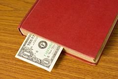 Dollar bill in book. Dollar bill used as a bookmark in a book Stock Photos