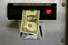 Dollar bill in a change machine. With please wait in red royalty free stock photo