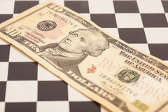 Dollar bill on a chess board Royalty Free Stock Photo