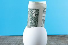 1 dollar bill in an egg shell. On a turquoise background. The co stock photos