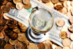 Dollar bill globe. Glass globe and reflection of   dollar bill and  pile of coins Stock Photos
