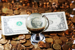 Dollar bill globe. Glass globe and reflection of   dollar bill and  pile of coins Royalty Free Stock Image