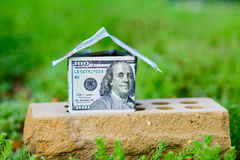 Dollar bill house on a brick Royalty Free Stock Photography