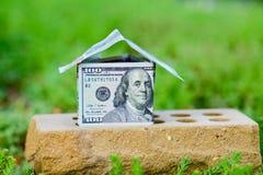 A dollar bill house on a brick Stock Photos