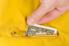 Dollar bill inside a pocket. Hand putting a dollar bill inside a pocket Royalty Free Stock Image