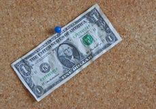 Dollar bill on peg board. A one dollar bill pinned to a cork peg board Stock Image