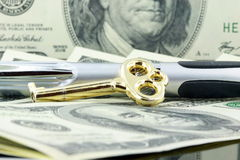Dollar bill with pen and gold key  Royalty Free Stock Images