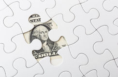 Dollar bill and puzzle piece Stock Image