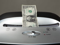 Dollar bill shredding. Concept photo of a dollar bill being shredded by a paper shredder depicting the weakened dollar value royalty free stock images
