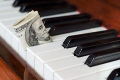 Dollar bill stuck in a piano. One hundred dollar bill stuck in a piano. Franklin stare. Earn from music Royalty Free Stock Images