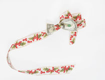 Dollar Bill Tied with Holly Ribbon. Holly ribbon tied around US dollar bill with trailing ribbon. Concept of squeezing the dollar to go further during the Stock Images