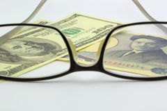 Dollar bill and yen with eyeglass Royalty Free Stock Photography