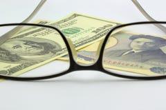 Dollar bill and yen with eyeglass. Dollar billa and yen with eyeglass Royalty Free Stock Photography