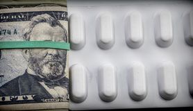 Dollar bills along with white pill package, conceptual image Stock Photos