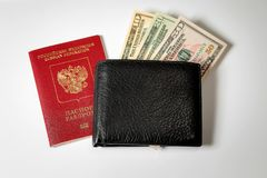 Dollar bills in a black men`s wallet and a passport of the Russian Federation stock photography