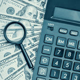 Dollar bills with a calculator and a magnifying glass Stock Images