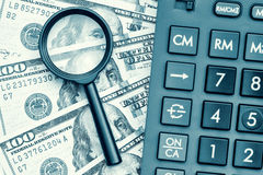 Dollar bills with a calculator and a magnifying glass Royalty Free Stock Image