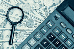 Dollar bills with a calculator and a magnifying glass Stock Photos