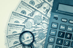 Dollar bills with a calculator and a magnifying glass Royalty Free Stock Images