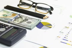 Dollar bills, calculator, pen, glasses, business charts are all on the table. Dollar bills, calculator, pen, glasses, business charts are all on the table Stock Photo