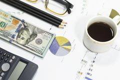 Dollar bills, calculator, pen, glasses, business charts are all on the table. Dollar bills, calculator, pen, glasses, business charts are all on the table Royalty Free Stock Photo