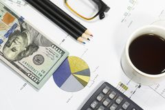 Dollar bills, calculator, pen, glasses, business charts are all on the table. Dollar bills, calculator, pen, glasses, business charts are all on the table Royalty Free Stock Image