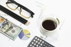 Dollar bills, calculator, pens, coffee、glasses and business charts are all on the table. Dollar bills, calculator, pens, coffee、glasses and business charts Stock Image