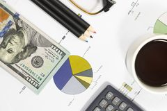 Dollar bills, calculator, pens, coffee、glasses and business charts are all on the table. Dollar bills, calculator, pens, coffee、glasses and business charts Stock Photography