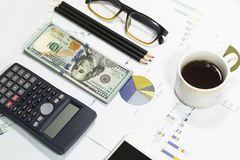 Dollar bills, calculator, pens, coffee、glasses, cellphone and business charts are all on the table. Dollar bills, calculator, pens, coffee、glasses Royalty Free Stock Photo