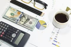 Dollar bills, calculator, pens, coffee、glasses, cellphone and business charts are all on the table. Dollar bills, calculator, pens, coffee、glasses Royalty Free Stock Photography