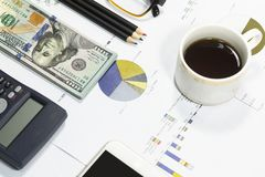Dollar bills, calculator, pens, coffee、glasses, cellphone and business charts are all on the table. Dollar bills, calculator, pens, coffee、glasses Stock Photography