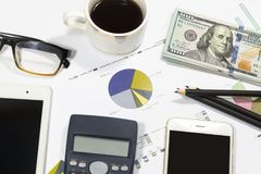 Dollar bills, calculator, pens, coffee、glasses, tablet, cellphone and business charts are all on the table. Dollar bills, calculator, pens, coffee、glasses Royalty Free Stock Image