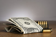 Dollar bills with cartridges Royalty Free Stock Photos