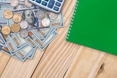 Dollar bills and coin with calculator pen. On desk Royalty Free Stock Photos