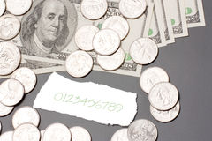 Dollar bills, coins. Hundred dollar bills, coins and a fragment of paper Stock Photos