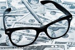 Dollar bills, eyeglasses and pen Royalty Free Stock Images