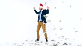 Dollars falling on formally dressed man in the Santa Claus hat. Dollar bills falling on formally dressed man in the Santa Claus hat stock footage
