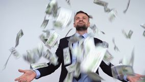 Slow motion of dollars falling on formally dressed man. Dollar bills falling on formally dressed man. Slow motion stock footage