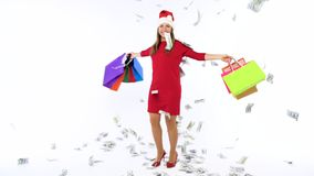 Dollar bills falling on Christmas shopping woman with multicolored shopping bags and crazy dancing on white background stock video