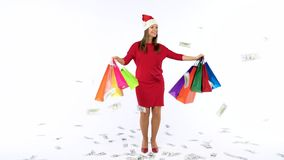 Dollar bills falling on Christmas shopping woman with multicolored shopping bags and crazy dancing on white background stock footage
