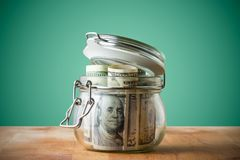 Dollar bills in glass jar isolated on a green background. Saving money concept for education stock images