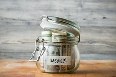 Dollar bills in glass jar isolated on wooden background. Royalty Free Stock Photography