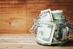 Dollar bills in glass jar on wooden background. Saving money concept. Stock Images