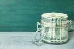 Dollar bills in glass jar on wooden table. royalty free stock photography