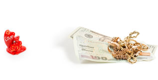 Dollar bills, gold jewellery and love Stock Photos