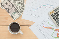 Dollar bills, graph, calculator and coffee on wood table Royalty Free Stock Photos