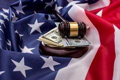 100 dollar bills and a hammer of judges placed on the American flag. 100 - dollar bills and a hammer of judges placed on the American flag royalty free stock images